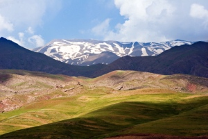 The countryside of Iran--flowing green hills and snow-capped mountains.