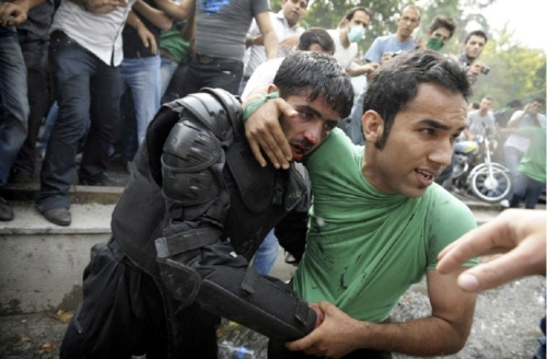 "A ""green"" support of Mousavi helps one of the injured riot police out of the crowd."